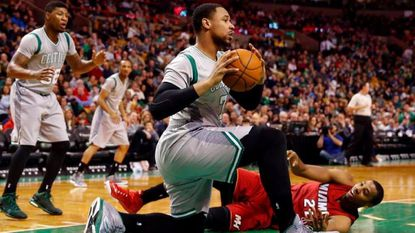 Jared Sullinger gathers in the ball in front of fallen Miami Heat's Hassan Whiteside during the first half of an NBA basketball game in Boston, Sunday, Feb. 1, 2015.