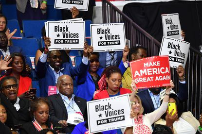 """The late Herman Cain and supporters of President Donald Trump """"Black Voices"""" listen to him speak during a campaign rally at the BOK Center on June 20, in Tulsa, Oklahoma."""