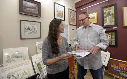Mat About You owner Charles Gruss, who reopened his store in Ellicott City after last year's flood, chats with Joan Grauman about her adult coloring book of sketches depicting Ellicott City.