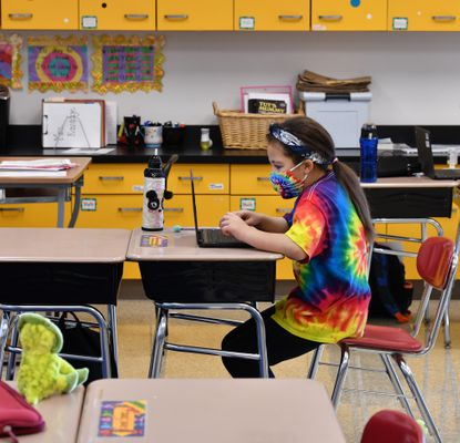 Wearing her matching tie-dyed mask, Prospect Mill Elementary School third grader Krynn Robinson works on her lesson in class last month. Enrollment at Harford County Public Schools has decreased by about 1,000 this year, with more students doing home schooling or enrolling in private schools due to virtual learning.