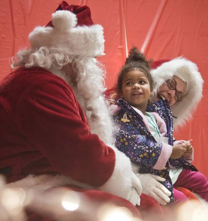 Ayla Bayly 4, meets Mr. and Mrs. Claus at Odenton Volunteer Fire Company during a Cookies and Crafts event with Santa to collect toys and funds for the needy. Santa is portrayed by Jeremy Weiss and Mrs. Claus by his wife Bridgette Weiss.