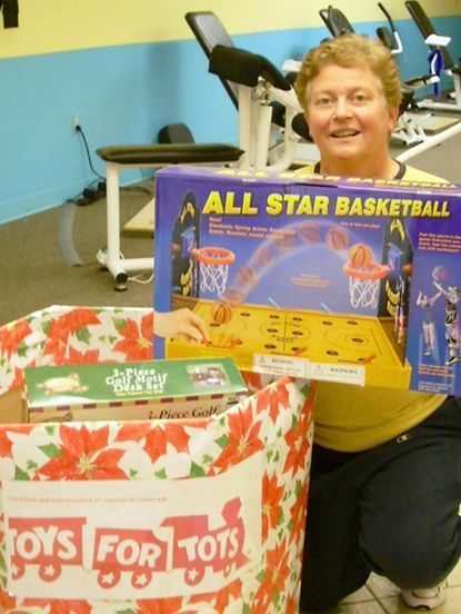 Suzy Hill, owner of Curves of Glenelg, surveys the loot that has been collected for the U.S. Marine Corps Foundation's Toys for Tots holiday drive. During the first week of collection, Suzy Hill counted more than 90 toys and games. By the time representatives from the Marines came for a second pick up at Curves in Glenelg, the amount of playthings had doubled.