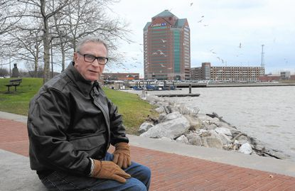Ed Hale sits on a ledge in Canton Waterfront Park, which is the site of the first lot he purchased in the city 39 years ago.