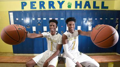 Perry Hall juniors Laquill Hardnett, left, and Anthony Higgs sit in their high school basketball team's locker room.