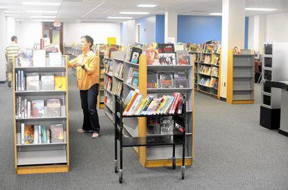 Library staffer Tina Korte shelves returned books at the temporary Laurel library on Sandy Spring Road.