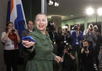 In a photo from Thursday, Dec. 8, 2011, then-U.S. Secretary of State Hillary Rodham Clinton hands off her mobile phone after arriving to meet with Dutch Foreign Minister Uri Rosenthal at the Ministry of Foreign Affairs in The Hague, Netherlands.