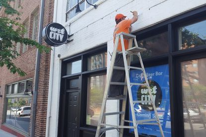 A painter touches up the exterior of Wet City, a new craft beer bar opening where Dougherty's Pub previously stood.