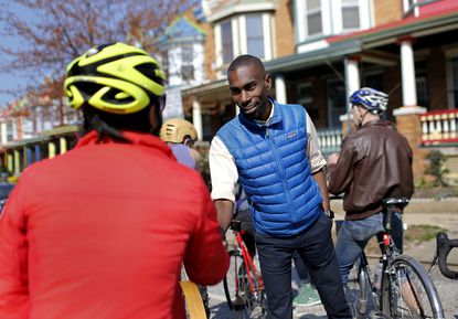 Baltimore mayoral candidate DeRay Mckesson, right, chats with bicyclists as he canvasses in the Charles Village neighborhood of Baltimore.