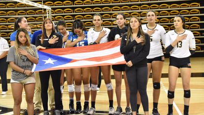 Puerto Rico natives and members of the Towson, Hofstra and UMBC women's volleyball teams stand for the Puerto Rican anthem next to the flag before the Tigers' game last Friday against Hofstra.