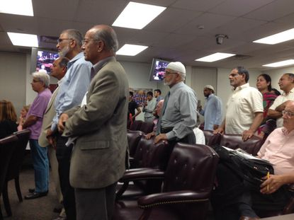Members of the Muslim community stand during the Baltimore County school board's vote on whether to close schools during the Muslim holidays.