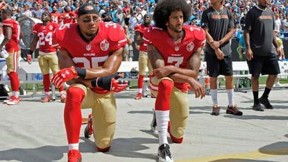 San Francisco 49ers' Colin Kaepernick (7) and Eric Reid (35) kneel during the national anthem before an NFL football game against the Carolina Panthers in Charlotte, N.C., Sunday, Sept. 18, 2016.