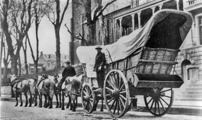"""A six-horse team pulled this Conestoga wagon pictured at an unknown location at an unknown time period. One teamster is riding horseback while the other is standing on the """"lazy board"""" where he can access the brake handle."""