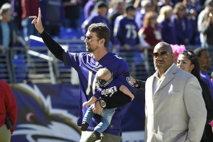 Olympic swimmer Michael Phelps, holding his son, Boomer, waves to the crowd before an NFL football game between the Baltimore Ravens and the Washington Redskins, Sunday, Oct. 9, 2016, in Baltimore. (AP Photo/Nick Wass)