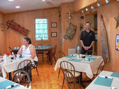 Dennis Funk, of White Hall, stands inside a knotty pine paneled dining room at The Weekender, the restaurant he opened in July with his White Hall neighbor Mike O'Connor.