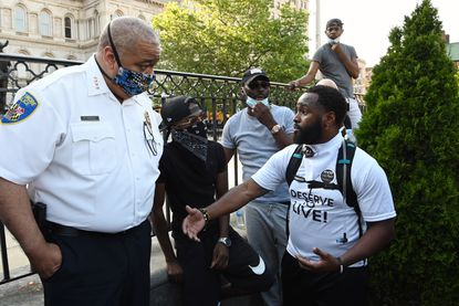 Baltimore Police Commissioner Michael Harrison listens to a question from Wesley Hawkins, of The Nolita Project, at a rally at City Hall last month to remember George Floyd and other African Americans killed by police and to demand change.