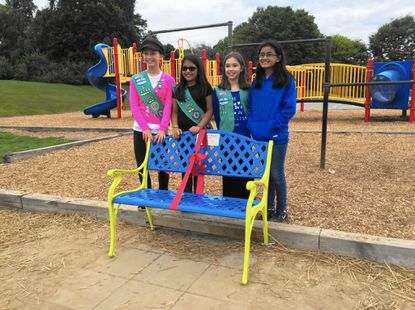 From left to right, Aria Lunt, 11, Simran Kalia, 10, Hailey Condron, 11, and Shriya Menon, 11 stand behind the friendship bench they created before the ribbon-cutting ceremony on Monday afternoon.