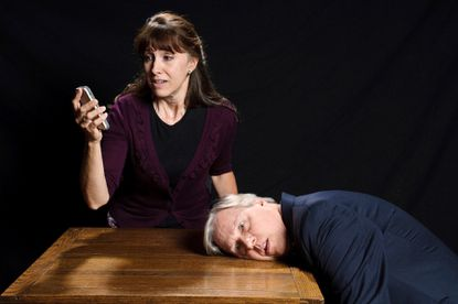 """Heather Quinn, as Jean, hesitantly answers the cell phone of heart attack victim Gordon, played by Jim Reiter, in the Colonial Players production of """"Dead Man's Cell Phone."""""""