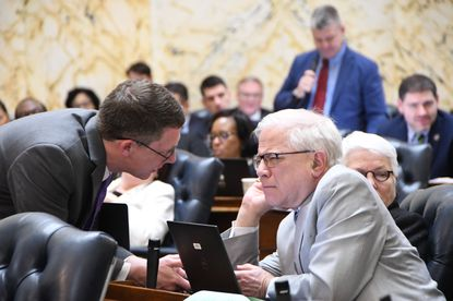 Democratic delegates Eric Luedtke, left, and Sandy Rosenberg talk Friday, March 6, 2020, during a House of Delegates debate on a bill requiring additional programs and spending in public schools. In the background, Republican Del. Mark Fisher of Calvert County implores lawmakers to support his amendment to the bill.