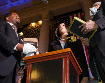 Baltimore City Councilman Nick Mosby, left, holds a bible as new State's Attorney Marilyn J. Mosby is sworn in by Robert Bell, a former chief judge.