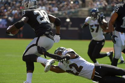 Oakland Raiders' Latavius Murray (28) escapes Baltimore Ravens' Jimmy Smith (22) during the first quarter in Oakland. Baltimore remains winless after losing to the Raiders, 37-33.