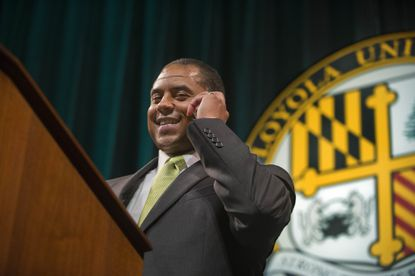 New Loyola men's basketball coach G.G. Smith talks to his father, Tubby Smith, on his cell phone during an event at Reitz Arena announcing the hiring.