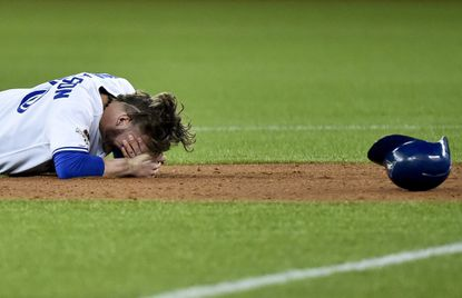 Toronto Blue Jays' Josh Donaldson rests after a collision during a force out at second base by Texas Rangers' Rougned Odor during the fourth inning of Game 1 of the American League Division Series in Toronto on Thursday, Oct. 8, 2015. Texas won, 5-3.
