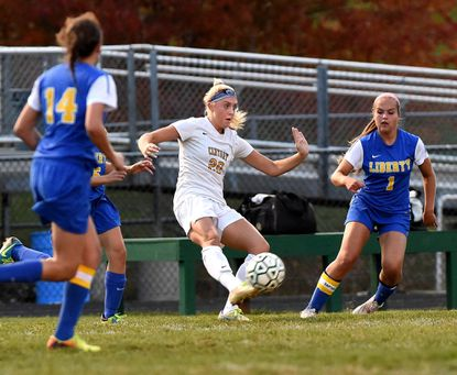 Century's Hannah Warther, center, plays the ball up the field in front of Liberty defenders.