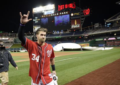 Washington Nationals' Bryce Harper walks to the dugout and reacts to the stands after hitting a walk-off double in the 12th inning against the Philadelphia Phillies, Saturday, Sept. 26, 2015, in Washington.