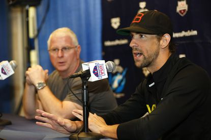 Michael Phelps, right, answers a question as his coach, Bob Bowman, looks on at a press conference at the Arena Pro Swim Series swim meet in Charlotte, N.C., on Thursday, May 14, 2015.