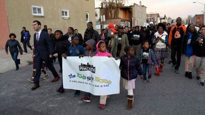 Young people and adults march through West Baltimore in support of the city's new $12 million youth fund in November. The city is set to hand over control of the fund to Associated Black Charities.