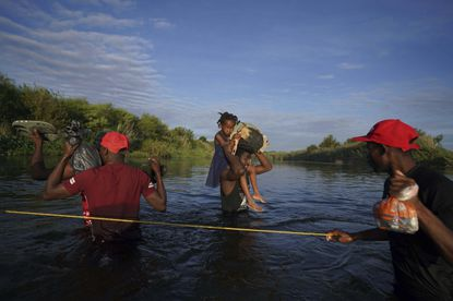 A man carries a little girl, who is clutching her Barbie doll, over the Rio Grande river toward Del Rio, Texas, early Wednesday, Sept. 22, 2021, as other migrants return to Ciudad Acuna, Mexico, some to avoid possible deportation from the U.S. and others to load up with supplies. (AP Photo/Fernando Llano)
