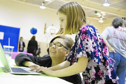 "Olivia Bowers, 9, a third-grader at Lansdowne Elementary School, shows Robin Franklin, a teacher at Relay Elementary who lives in Catonsville, how to use a computer program during Lansdowne Elementary's ""Night of Innovation."""