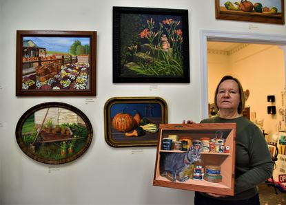 Ona Martin is pictured with her paintings on exhibit at Offtrack Art Cooperative and Gallery in Westminster.
