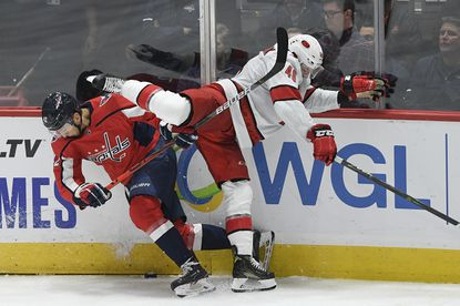 Washington Capitals defenseman Martin Fehervary (42) battles for the puck against Carolina Hurricanes left wing Jordan Martinook (48) during the third of an NHL hockey game, Saturday, Oct. 5, 2019, in Washington. (AP Photo/Nick Wass)