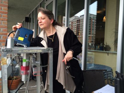 Johns Hopkins School of Public Health researcher Ana Rule checks air monitoring equipment she set up outside the Inn at The Black Olive. The family operating the hotel is concerned about development across the street at Harbor Point and wants to independently monitor chromium levels in the air.