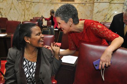 Sen. Lisa Gladden, left, greets newcomer Sen. Cheryl Kagan in the Senate chamber before the opening of the 2015 legislative session.