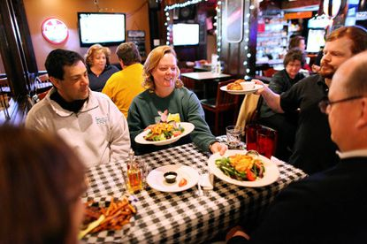 Corey Hall, right, of Columbia serves food to Alison Klump, left, Kiran Talsania, Cris Talsania, center, and Lee Klump, all of Silver Spring, at Second Chance Saloon in Columbia on Saturday, March 2
