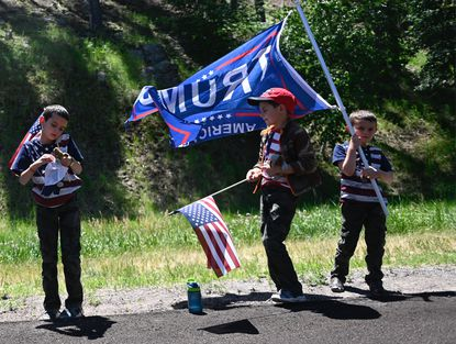 Supporters of U.S. President Donald Trump wave flags on a road in Keystone, South Dakota, on July 3, before a fireworks celebration for the Fourth of July holiday at Mount Rushmore National Monument and the visit of US President Donald Trump.