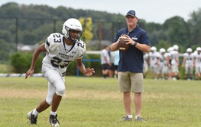 Manchester Valley head football coach Bernie Koontz throws passes to senior Nathaniel Costley and the group of running backs during a team practice at the school on Monday, August 26.