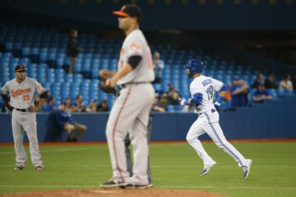 Jose Bautista circles the bases after hitting a two-run home run in the seventh inning. Jason Garcia and Manny Machado (13) look on.