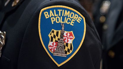 The Baltimore Police patch on a graduated trainee's uniform. A pit bull was shot by police after attacking two people in South Baltimore.