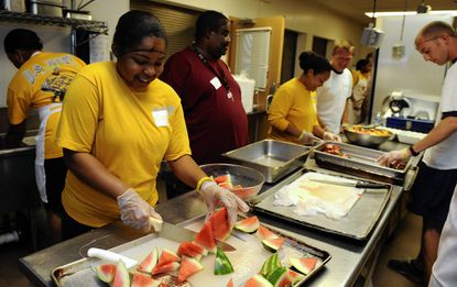 Gabby Johnson, left, a sailor on the USS San Antonio, slices watermelon at Baltimore Station shelter. She and others who were in the city for Sailabration volunteered.