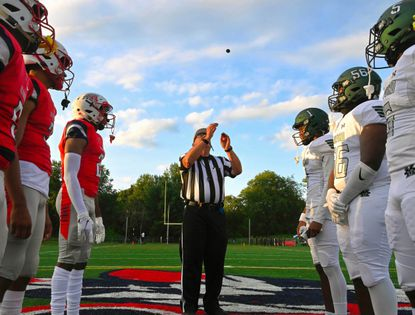 Captains from Franklin and Milford Mill High Schools watch as the referee flips the first coin toss of the 2021 football season.