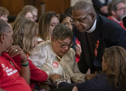 Pastor Jackie Jackson, right, an anti-violence advocate from Cincinnati, is joined by gun violence survivor Mia Livas Porter, lower right, of Los Angeles, as they comfort Rev. Sharon Risher, center, whose mother was killed in the shooting at the Emanuel AME Church shooting in Charleston, S.C., during a House Democratic forum urging the Senate to vote on a bill that would expand background checks for gun purchases, on Capitol Hill in Washington, Tuesday, Sept. 10, 2019. (AP Photo/J. Scott Applewhite)