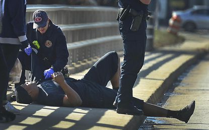 A Charlotte firefighter tends to Panthers quarterback Cam Newton following a crash in uptown Charlotte.