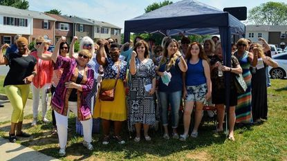 Donna Kropp, center, does the Rosie the Riveter pose at her house dedication ceremony along with Habitat Susquehanna Executive Director Karen Blandford, left, family members, Habitat staff and sponsors.