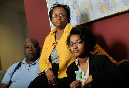 From left, the Rev. William Warr, his wife Angela and granddaughter Cortavia Harris, the family of Jazimen Warr, sit with a photo of Jazimen at the office of attorney Andrew Bederman, not pictured, in Silver Spring on March 8. Jazimen Warr was killed by a drunk driver in 2008.