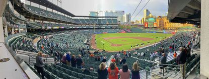 Baltimore Orioles fans stand, distanced because of coronavirus regulations for the first of a three-game series against the Oakland Athletics at Oriole Park at Camden Yards Fri., April 23, 2021. (Karl Merton Ferron/Baltimore Sun Staff)