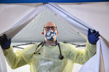 March 27 -- Dr. Richard Bruno, site medical director at Chase Brexton Health Care in Mt. Vernon, wears a colorful cloth mask over his N95 respirator. His wife, Mary Bruno, is making them for him and members of his staff to boost morale. Bruno is in the door way of one of the COVIC-19 testing tents near the entrance to the building. This tent, one of several set up by IronMark, sits in front of an old teller's cage from the building's former owner, Monumental Life Insurance Company.