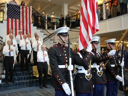"""The Calvary United Methodist Church Men's Choir sings """"The Star-Spangled Banner"""" as the Northeast High School Marine Corps Junior ROTC Color Guard presents the colors at the Veterans Day Celebration honoring 41 Veterans living at Brightview Senior Living in Annapolis."""